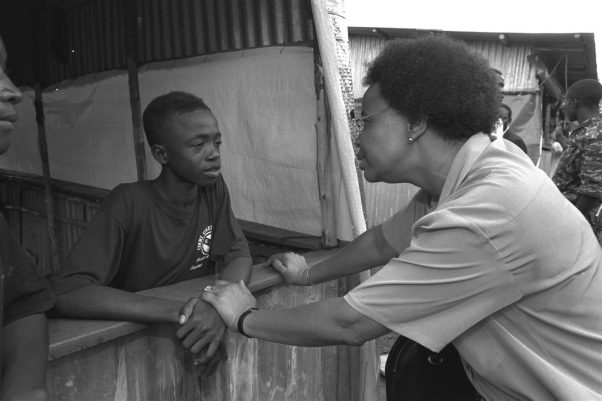 Graca Machel speaks with a former child soldier during a visit to a UNICEF-assisted camp for demobilized child soldiers near Freetown, the capital. The boy is 1 of approximatley 25 former child soldiers who had been forcibly conscripted by rebel forces.<br /> From 2-5 November 1995, Ms. Graca Machel visited demobilization centres for child soldiers, displaced persons' camps, and health and feeding centres set up in and near Freetown, the capital of Sierra Leone, part of her global work, appointed by United Nations Secretary-General Boutros Boutros-Ghali, to carry out a two year Study on the Impact of Armed Conflict on Children. The Study will be presented to the Secretary-General in the fall of 1996. The civil conflict in Sierra Leone, which began in 1991, has displaced over 40% of the country's 4.5 million inhabitants, already among the poorest in the world. Only 25% of eligible children attend school and 13% of children suffer from moderate to severe wasting. Up to 2,500 children have been combatants in the current conflict, many having been forcibly abducted from their homes. In addition to assisting with basic health, education and water services, UNICEF is also supporting a programme, together with NGO's and other partners, to demobilize and rehabilitate former child soldiers.